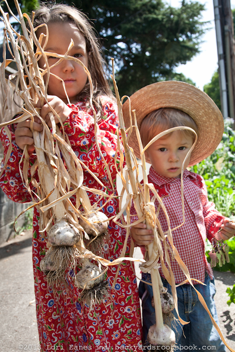 Fia and Xoco hold freshly pulled garlic from their Portland garden.