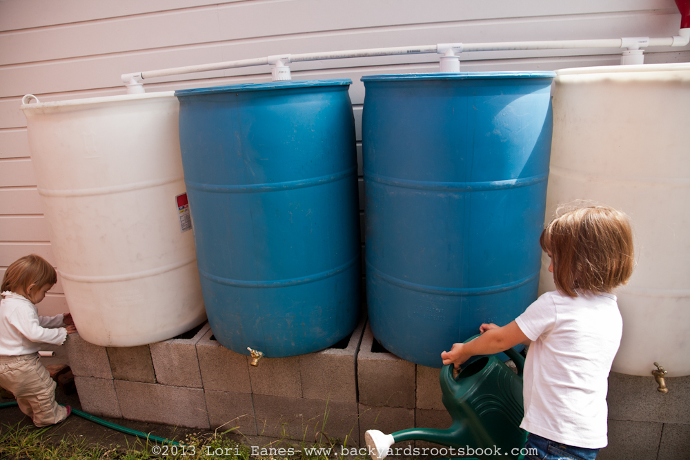 Two young girls collect water from rain barrels.